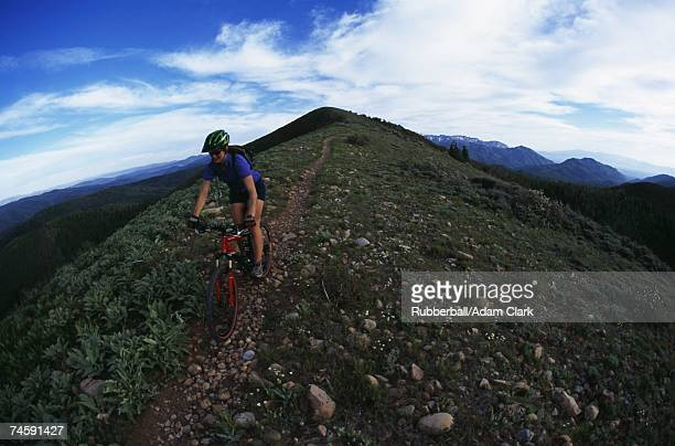 Woman riding mountain bike on hill with blue sky