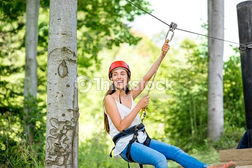 Woman riding on a zip line : Stock Photo