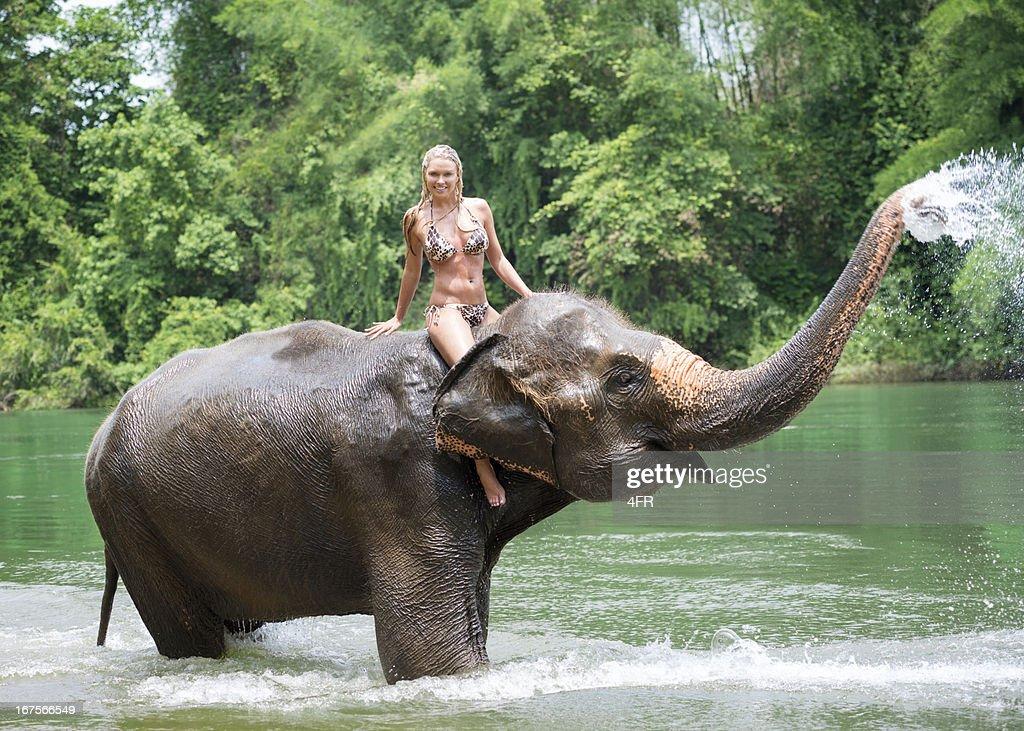 Woman riding on an Elephant, Tropical Rain Forest