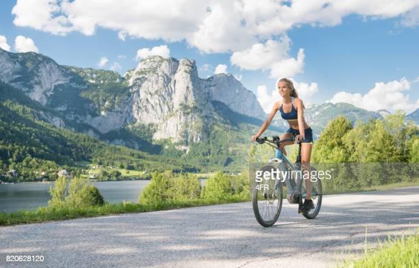 彼女の E-自転車・ マウンテン バイク、湖グルントルゼー、オーストリアに乗って女性