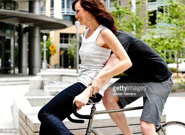 A woman riding on the handlebars of a bike as her friend tries to stay in control.