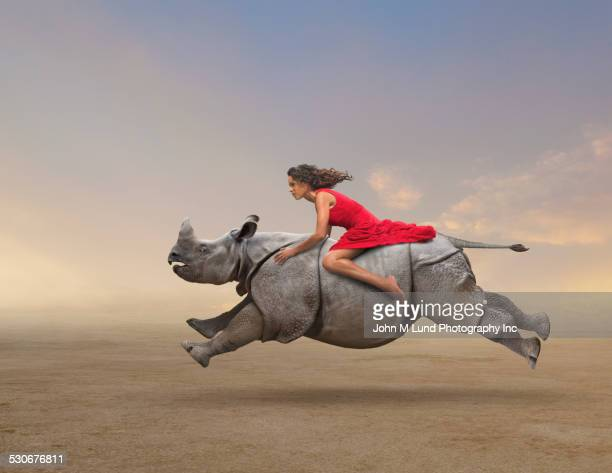 Woman riding rhinoceros in rural field