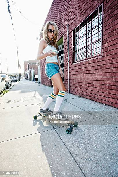 Woman riding skateboard on city street