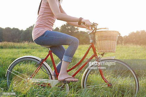 Woman riding vintage bike in countryside.