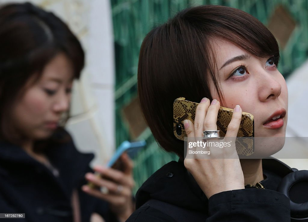 A woman, right, talks on her smartphone as other woman looks at her smartphone outside a train station in Tokyo, Japan, on Sunday, April 21, 2013. The number of smartphone subscribers in Japan surged to 37 percent of all contracts as of March 31 from 3 percent three years earlier, according to Tokyo-based MM Research Institute Ltd. Photographer: Yuriko Nakao/Bloomberg via Getty Images