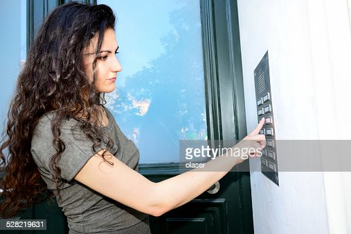 woman ringing door bell apartment building stock photo getty images