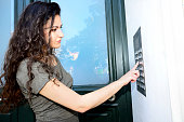 Woman ringing door bell apartment building