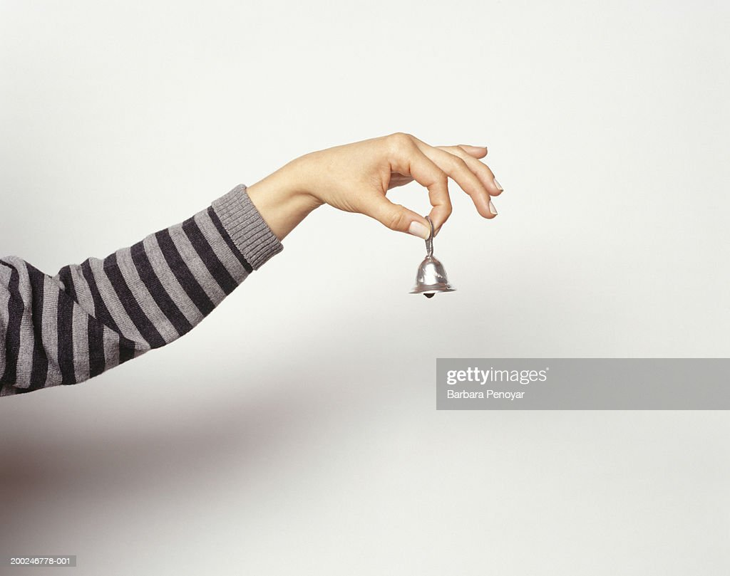 Woman ringing little bell, Close-up of hand