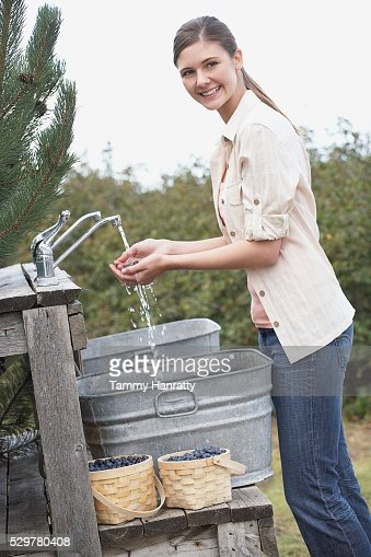 Woman rinsing blueberries : Stock Photo