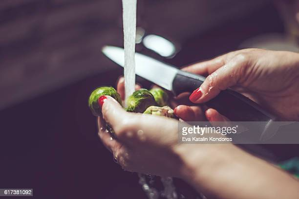 Woman rinsing brussels sprouts in the kitchen