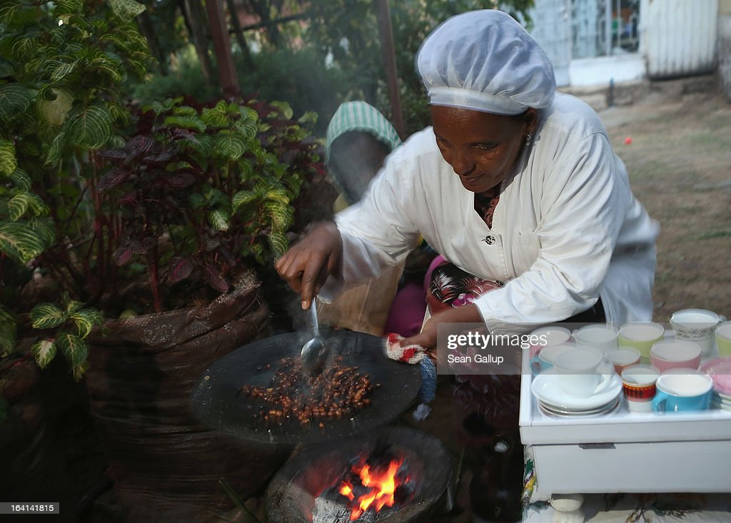 A woman roasts coffee beans to prepare traditional coffee for a visitor on March 19 2013 in Addis Ababa Ethiopia Ethiopia with an estimated 91...