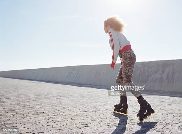 Woman roller blading with headphones on, low angle view