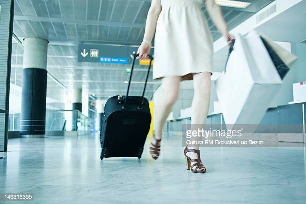 Woman rolling luggage in airport