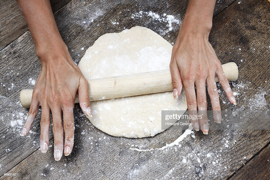 Woman rolling out fresh bread dough : Stock Photo