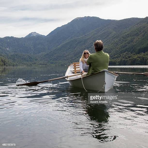 Woman rowing boat across lake