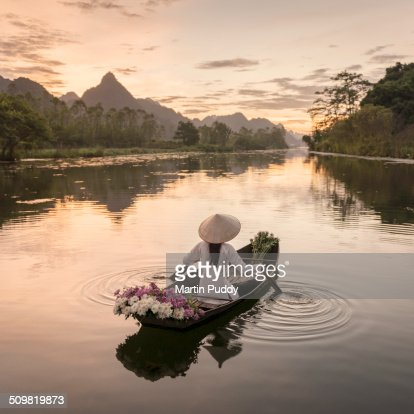 woman rowing boat along river, carrying flowers