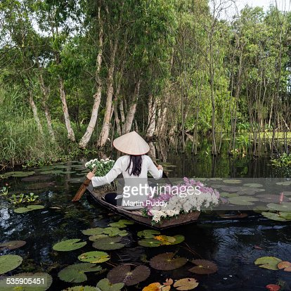 Woman rowing boat carrying flowers
