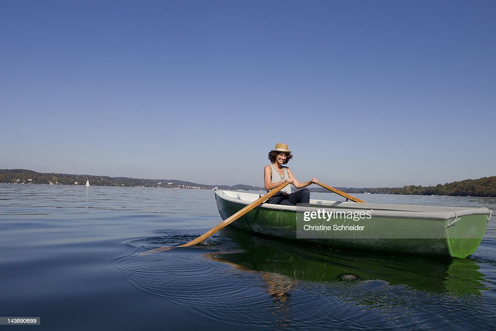 Woman rowing boat in still lake : Stock Photo