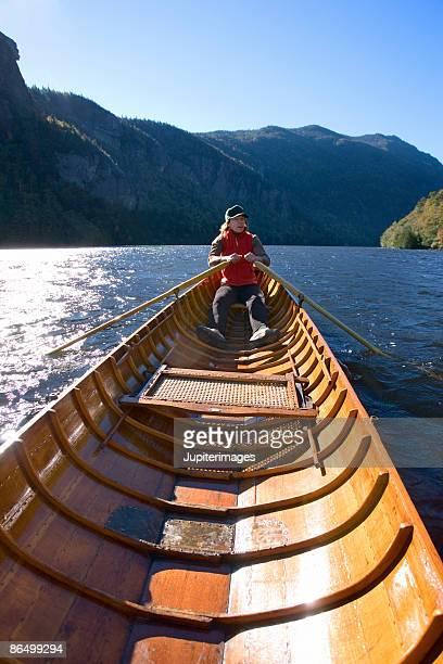 Woman rowing in canoe on lake, New York