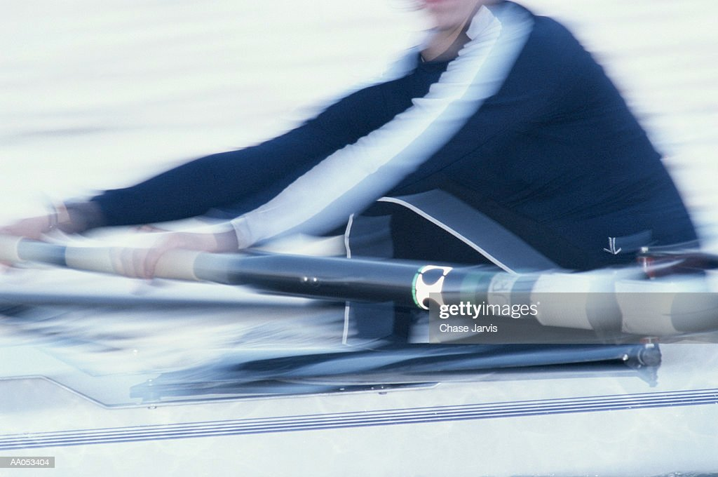 Woman rowing on crew team, mid section (blurred motion) : Stock Photo