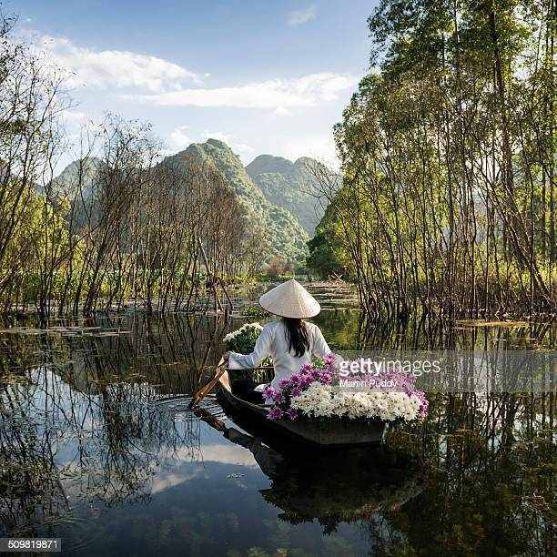 woman rowing small boat, carrying flowers