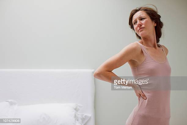 Woman rubbing aching back in bedroom