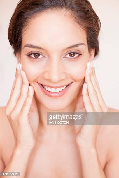 Woman rubbing cream into her face