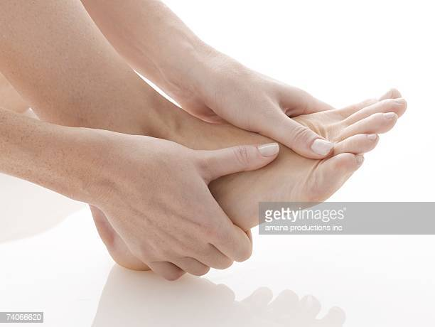 Woman rubbing her foot (close-up)
