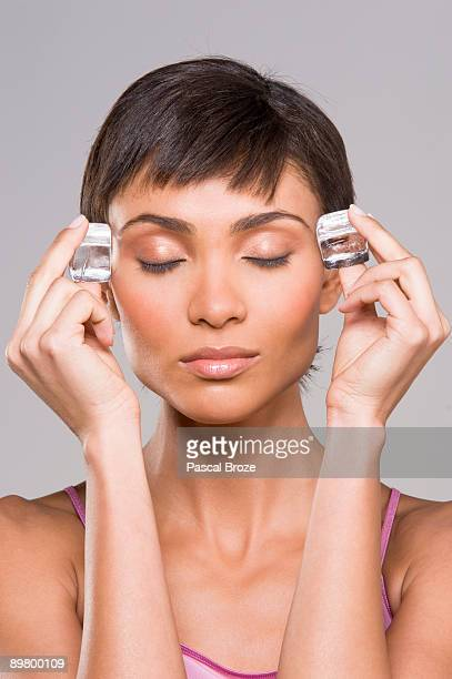 Woman rubbing ice cubes on her temples