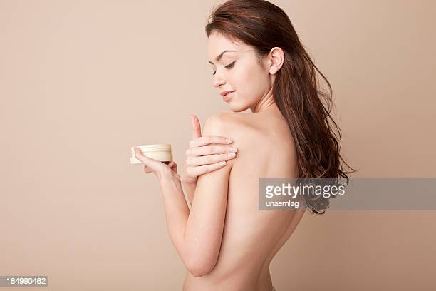 A woman rubbing lotion on her naked arm