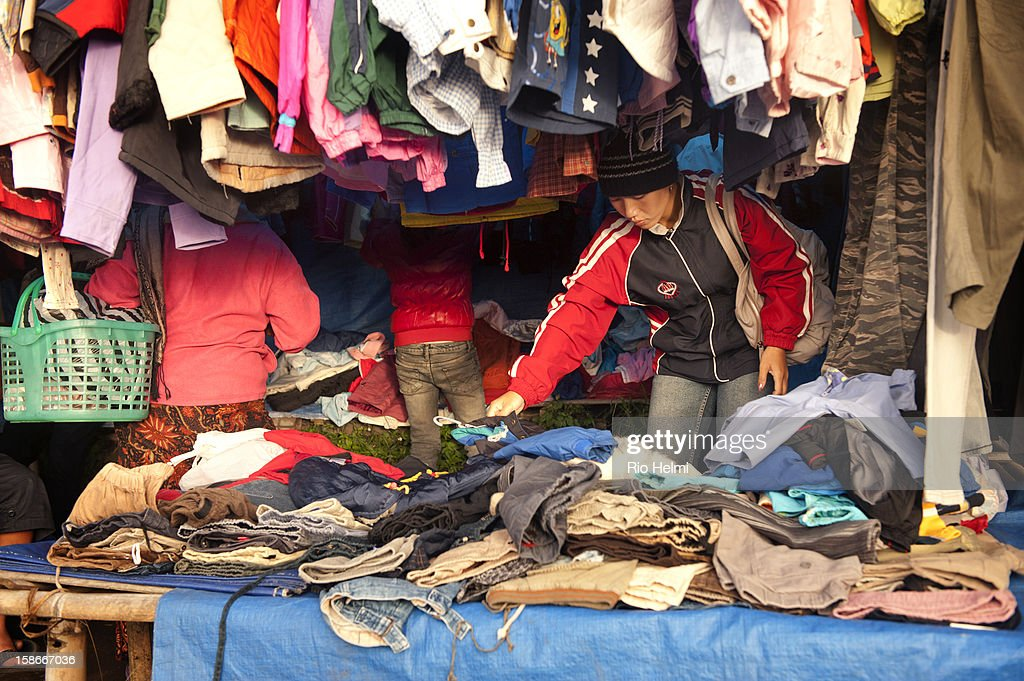MARKET, KINTAMANI, BALI, INDONESIA - : A woman rumages through a used clothing stall in the Kintamani market. A large percentage of Balinese villagers buy their everyday clothes from markets like this..