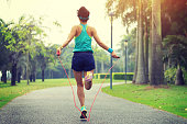 woman runner athlete jumping rope at tropical park