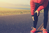 woman runner hold her injured leg on road
