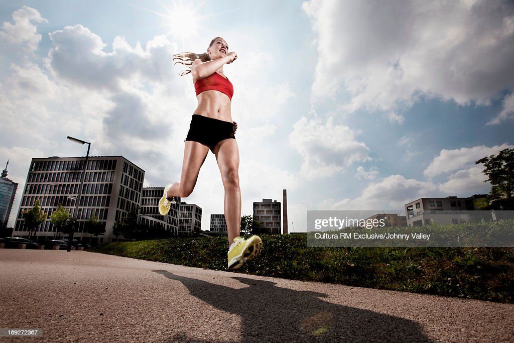Woman runner in mid stride : Stock Photo