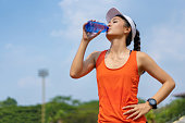 Woman runners are drinking water. After training