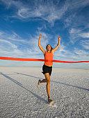 Woman running across finish line, Utah, United States