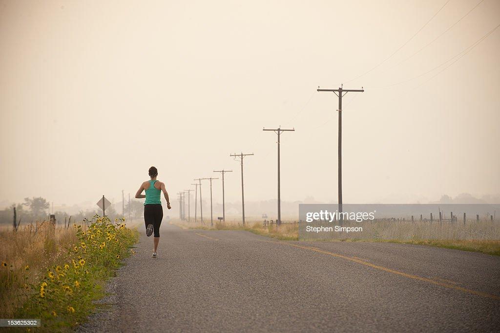 woman running along empty road, Summer morning : Stock Photo