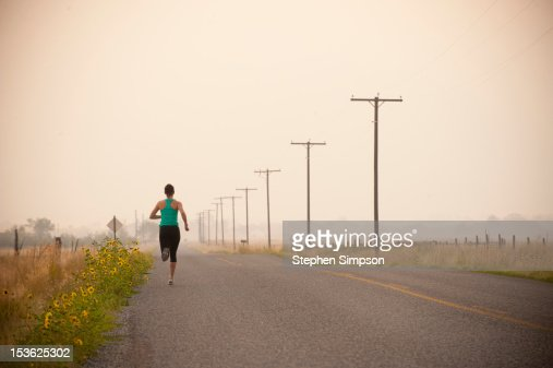 woman running along empty road, Summer morning : Stock Photo