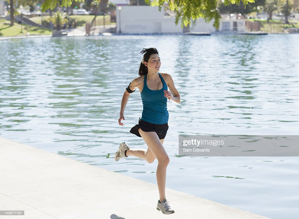 Woman running along lake in park : Stock Photo