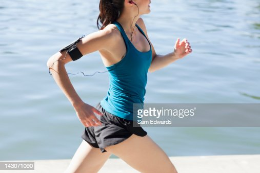 Woman running along lake : Stock Photo