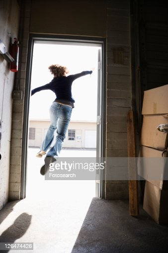 Woman Running And Jumping Through Open Door From Building