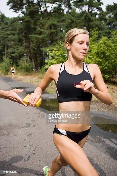 Woman running and reaching for wet sponge in sports race