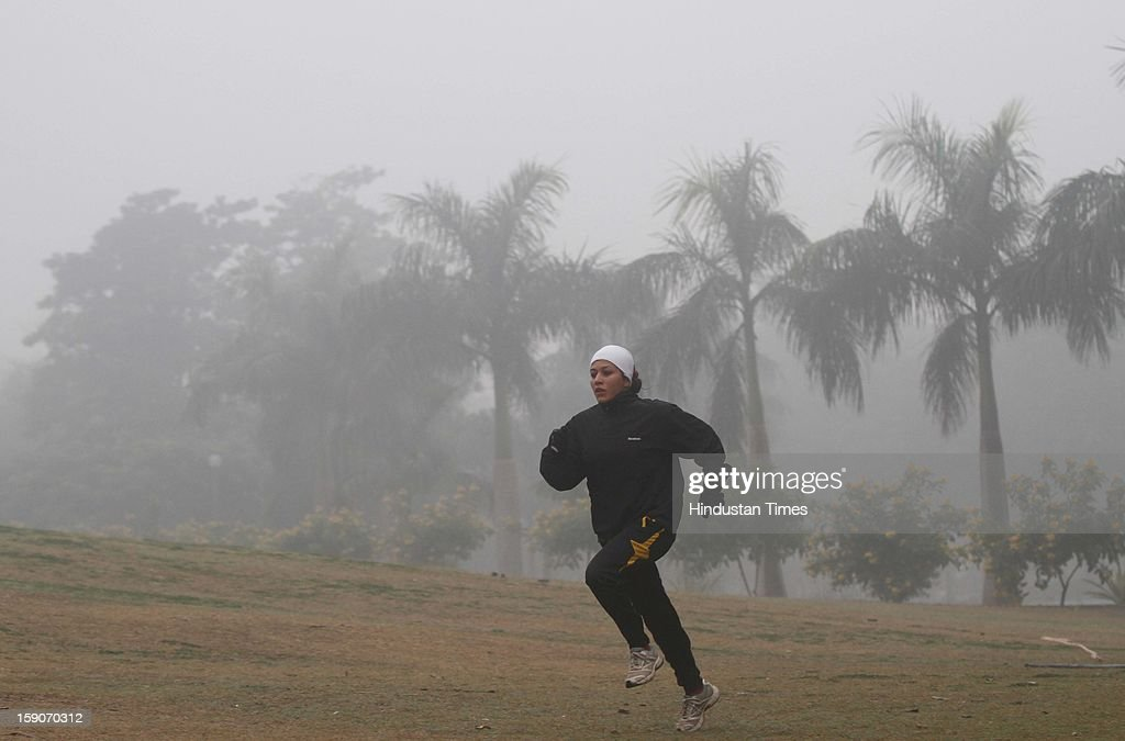 A woman running at Lodi Garden on a foggy and cold morning on January 7, 2013 in New Delhi, India. Dense fog and icy winds disrupted normal life as Delhi's minimum temperature settled at five notches below average at 2.4 degrees Celsius. Fog forced visibility to drop to about 500 metres in the morning resulting in 15 flights and 42 trains were delayed out of Delhi while 18 trains got cancelled.