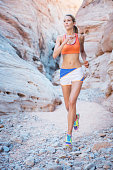 Woman running Cross Country through a Canyon