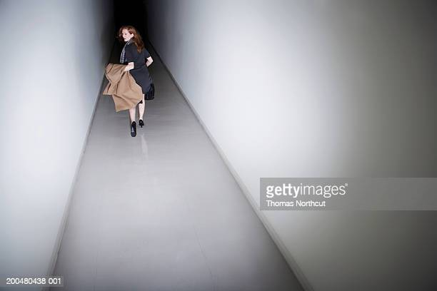 Woman running down corridor, looking over shoulder, rear view