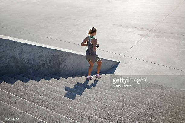 Woman running down steps in urban setting