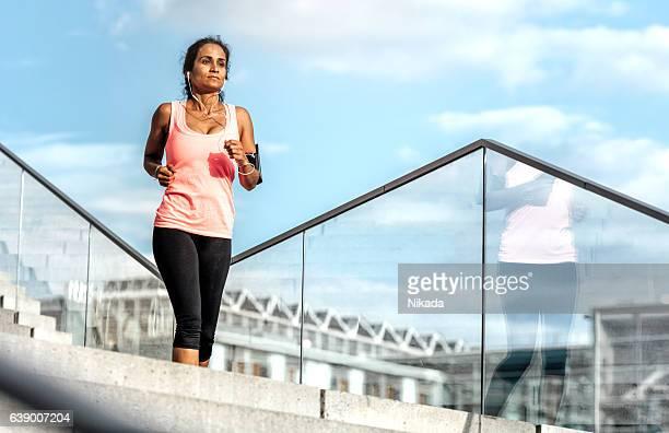 Woman running down steps in urban setting