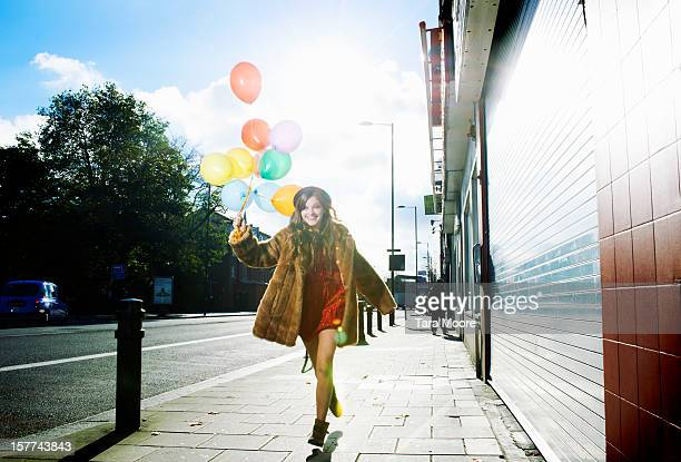 woman running down street holding balloons