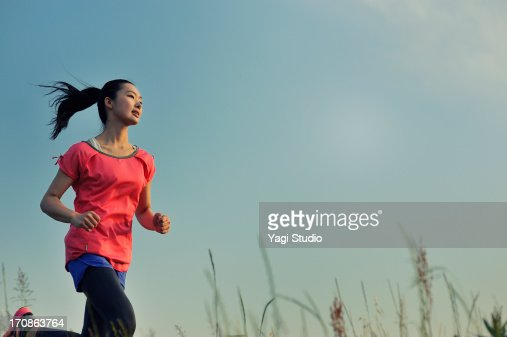 Woman running for exercise at sunset. : ストックフォト
