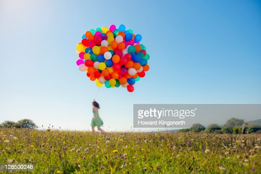 woman running holding big bunch of balloons : Stock Photo